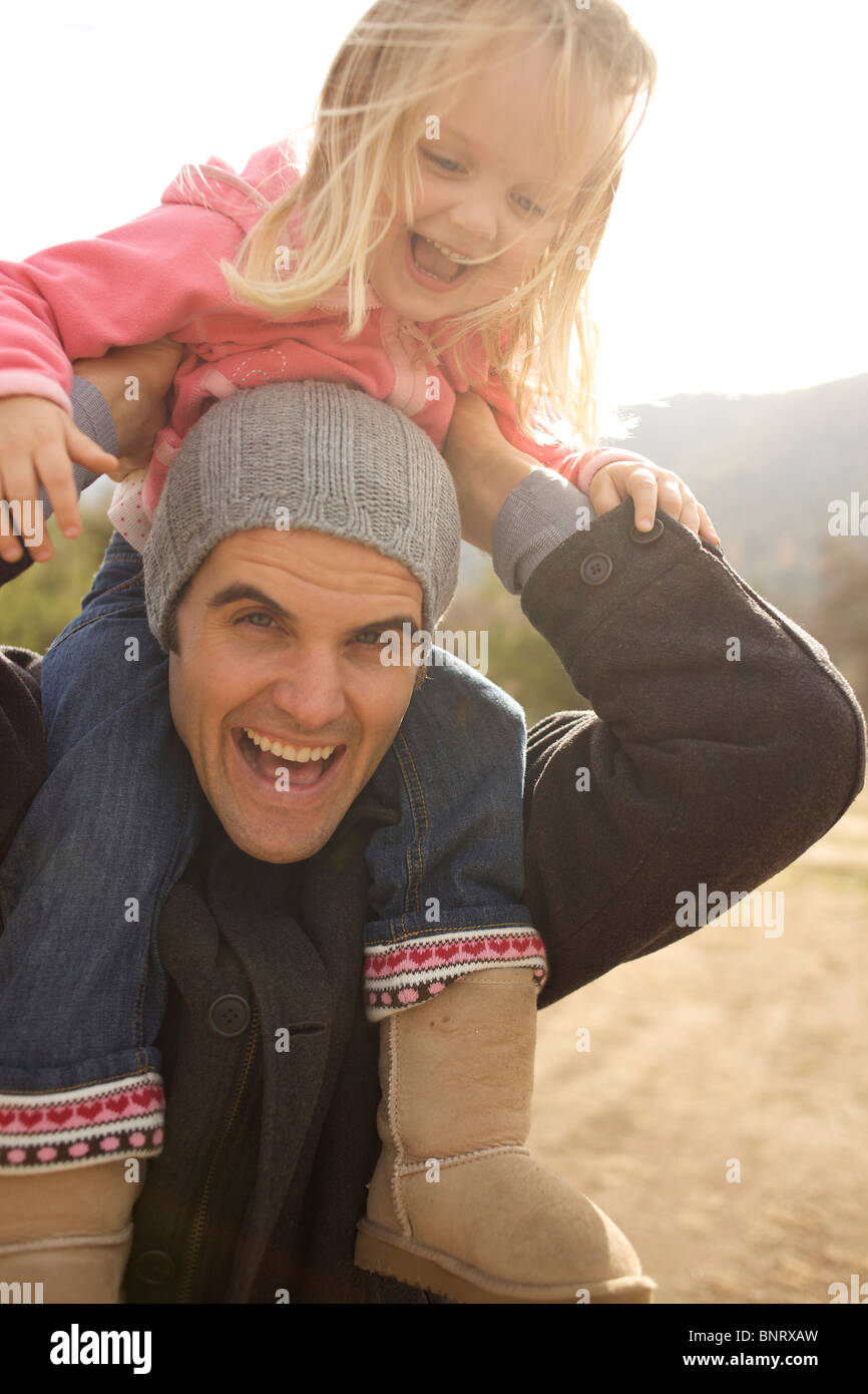 Young girl rides her uncle's shoulders. - Stock Image