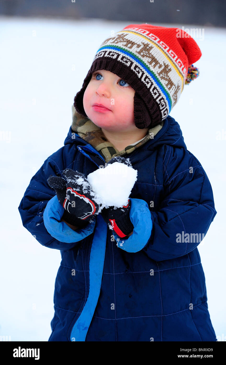 Toddler plays with snow in a snowsuit. - Stock Image