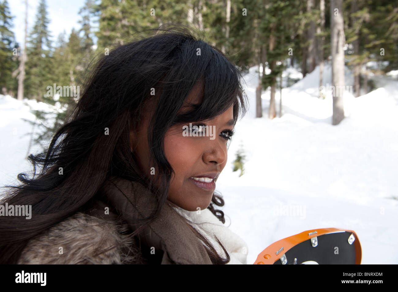 Portrait of a young African American woman holding snowshoes with snowy background. - Stock Image
