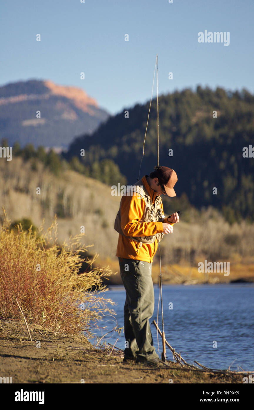 A man prepares a fly on the Gros Ventre River in Wyoming. - Stock Image
