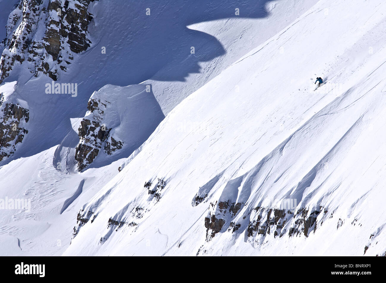 A man skis a steep line in Wyoming. - Stock Image