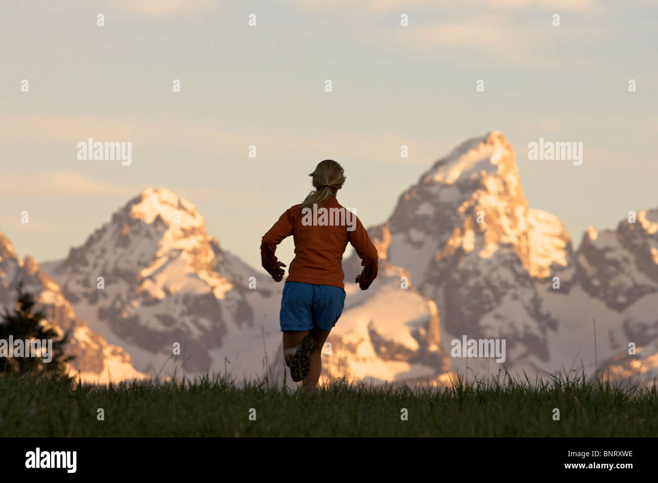 A woman runs on a trail in Wyoming. - Stock Image