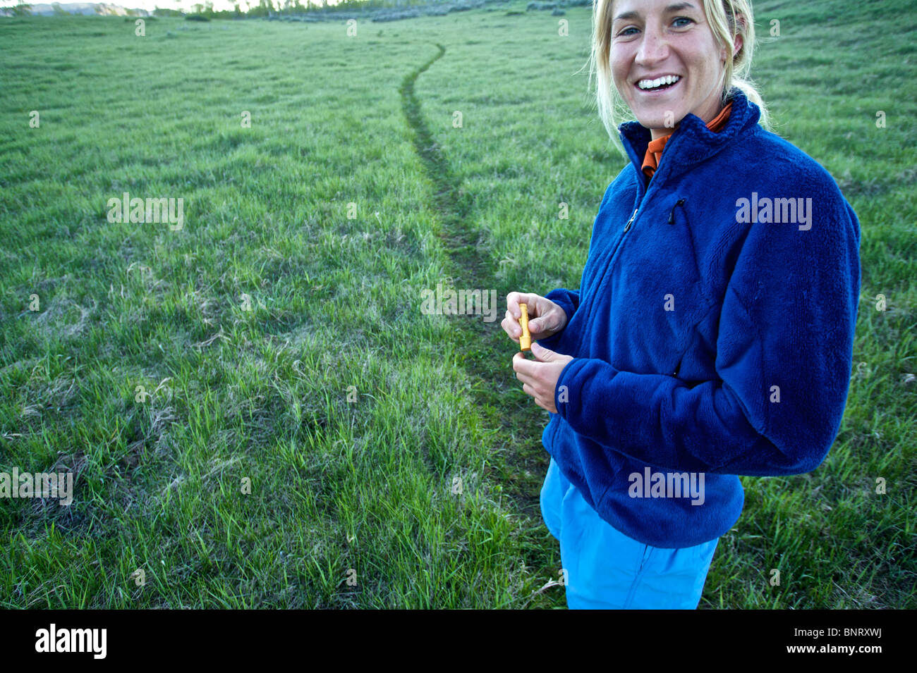 A woman breaks from trail running. - Stock Image