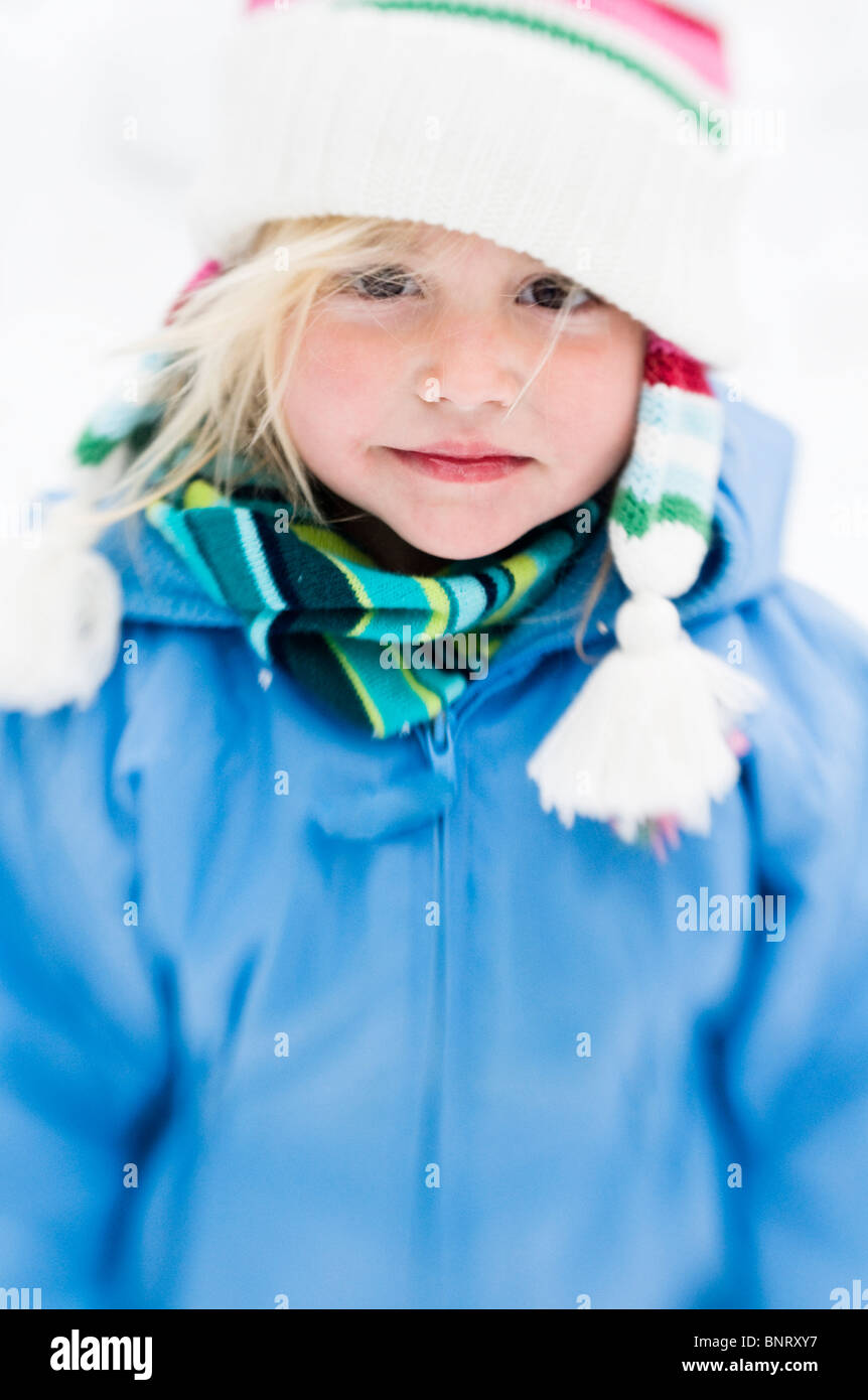 Young girl smilies with pink cheeks in the winter snow with select focus. - Stock Image