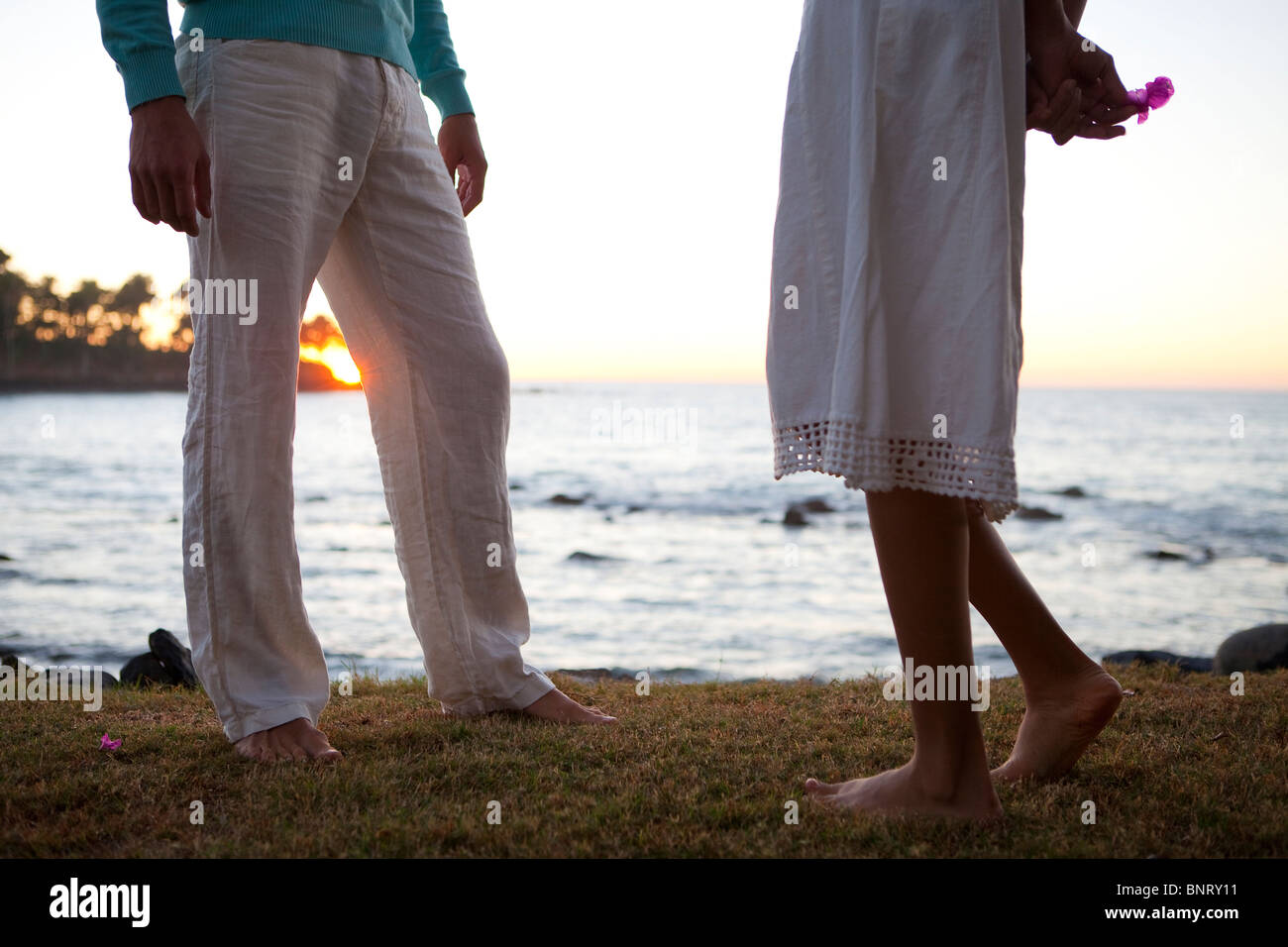 A man talks with a shy woman near the ocean at sunset. - Stock Image