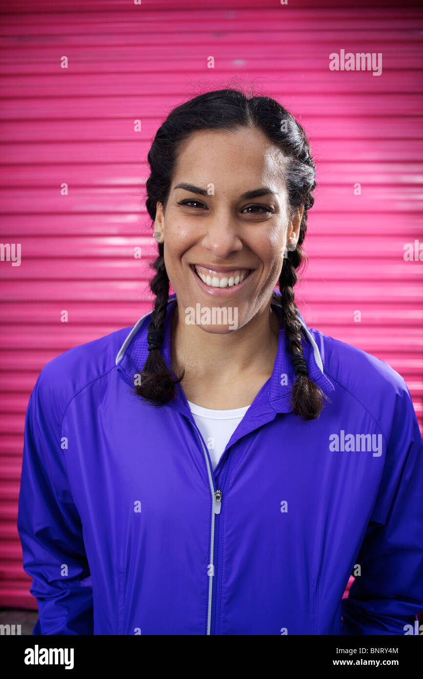 Young female runner wearing braids and a blue jacket stands in front of a pink door and smiles in San Diego. - Stock Image