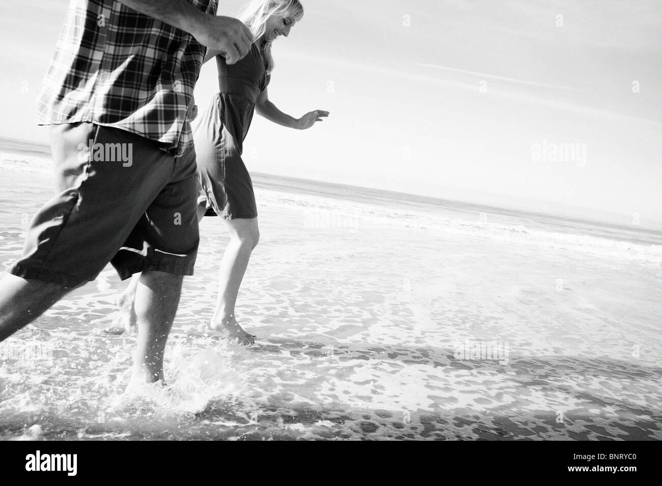 Couple run by the water and get their feet wet at the beach. Stock Photo