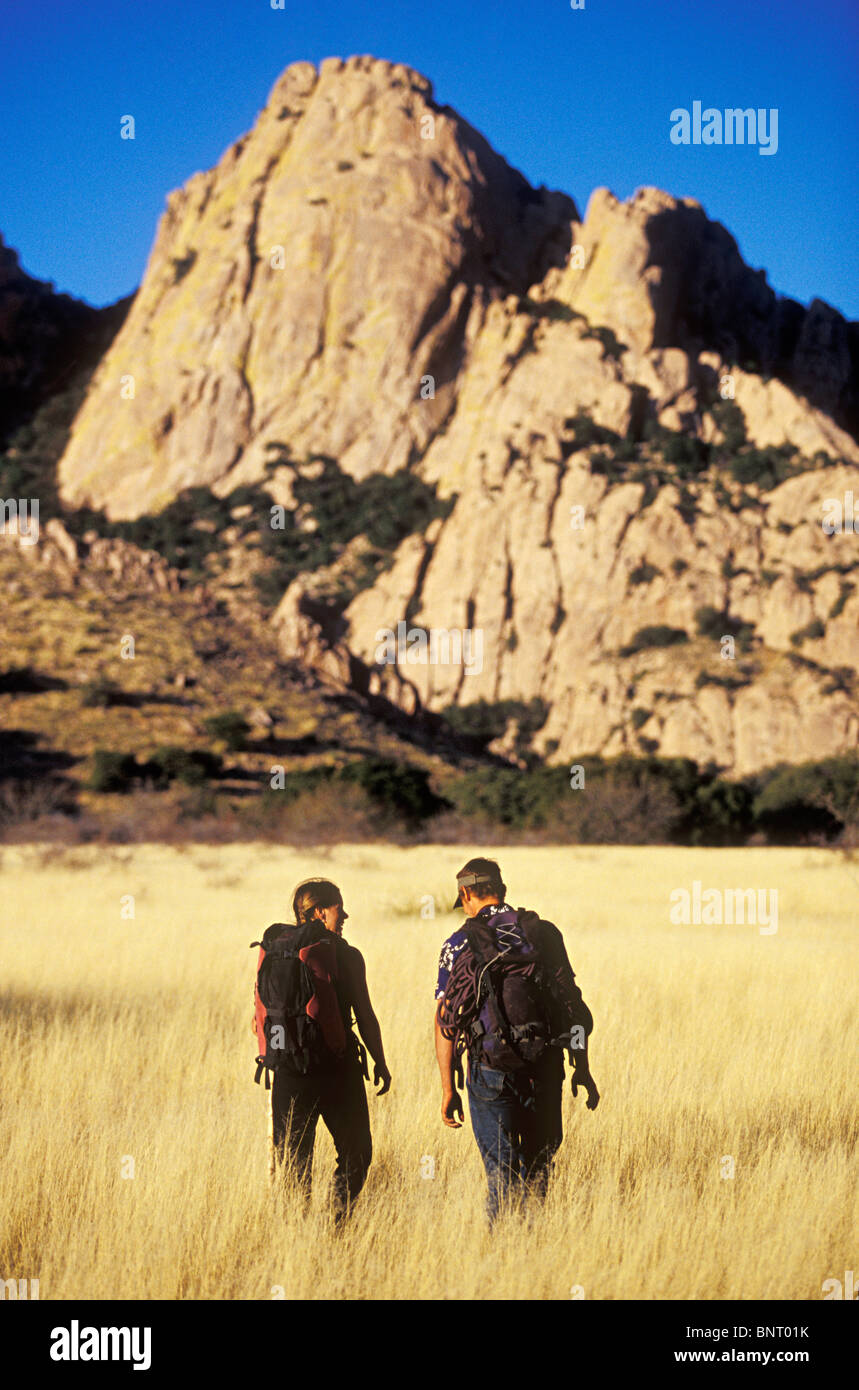 Man and women hiking through golden grass towards a mountain, Cochise Stronghold, Arizona. - Stock Image