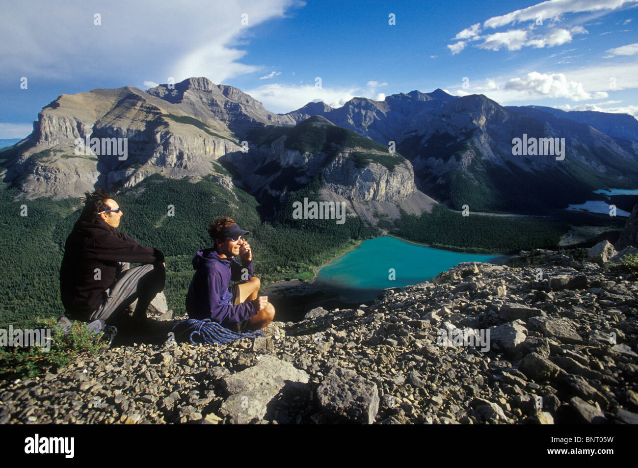 Two climbers stay in touch by talking on a cell phone in the mountains. - Stock Image