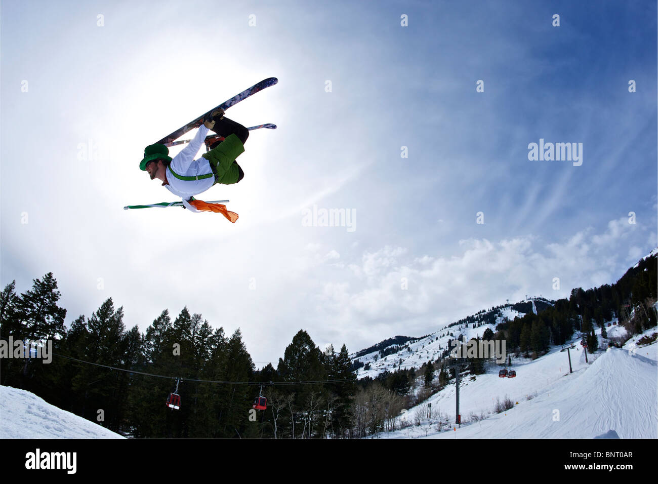 A man dressed as an Irish leprechaun jumps on his skis in Wyoming. - Stock Image