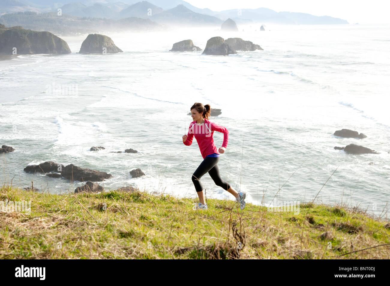 Woman trail running along the Oregon coast. Stock Photo