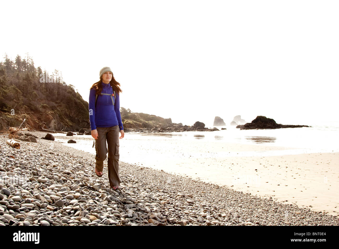 A woman hiking a secluded rocky beach. - Stock Image
