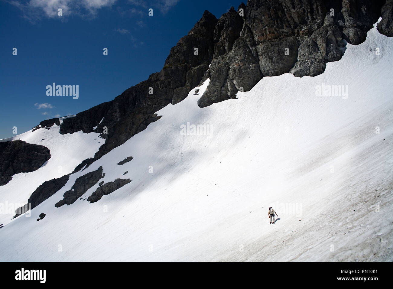 Man appears small on large snowfield in the mountains. - Stock Image