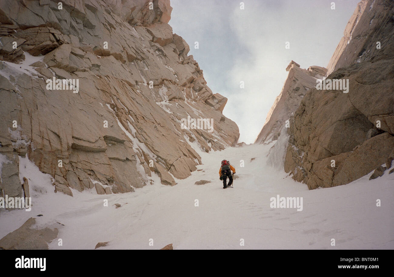Mountain climber in yellow jacket ascends steep snow gully. Stock Photo