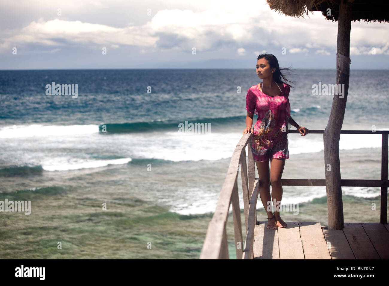 Young women in pink dress above tropical beach. - Stock Image