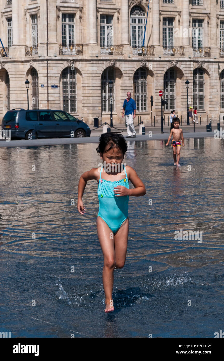 Little girl running, The Water mirror in front of the Stock Exchange Square, Bordeaux, France - Stock Image