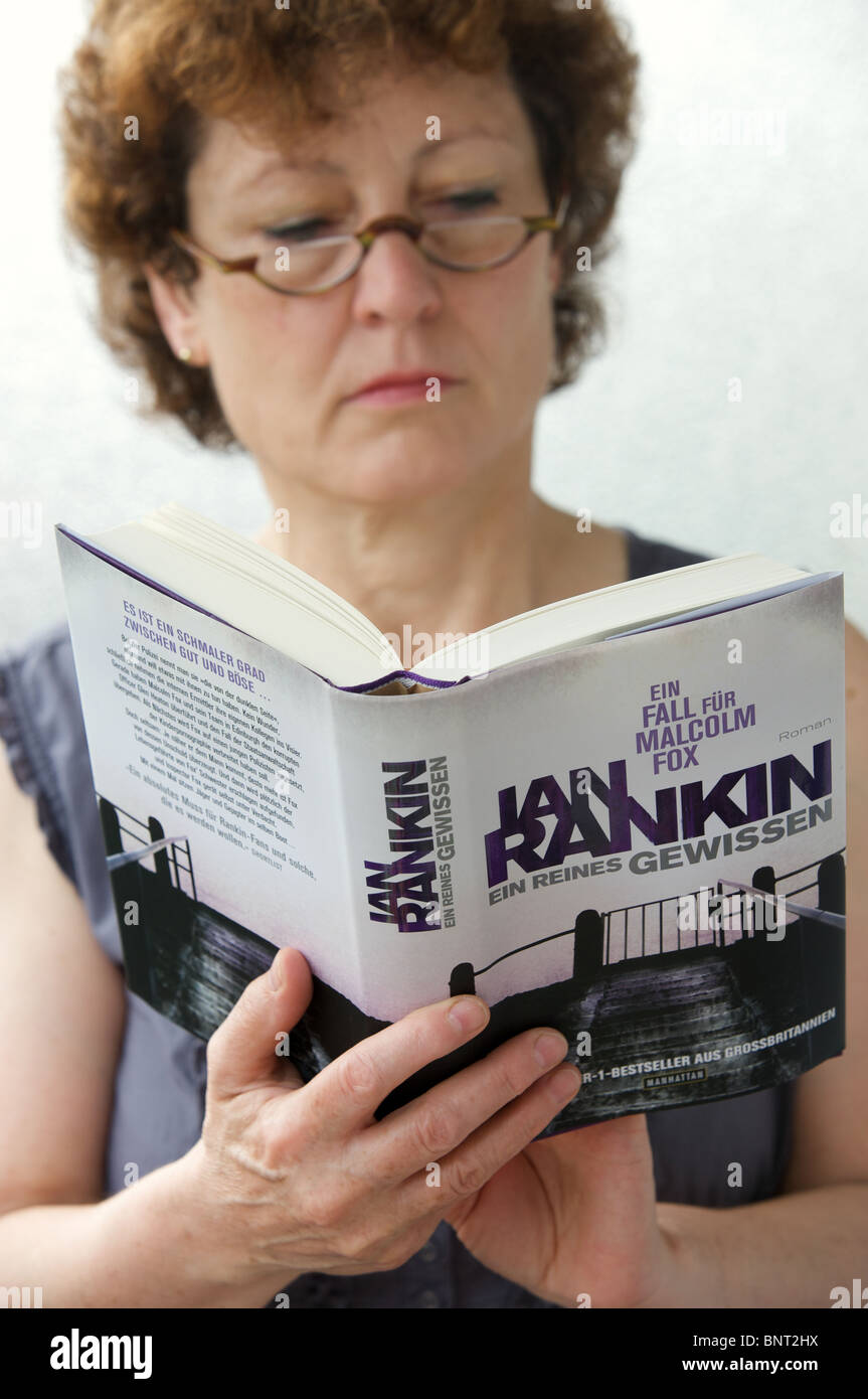 German woman reading an Ian Rankin novel - Stock Image