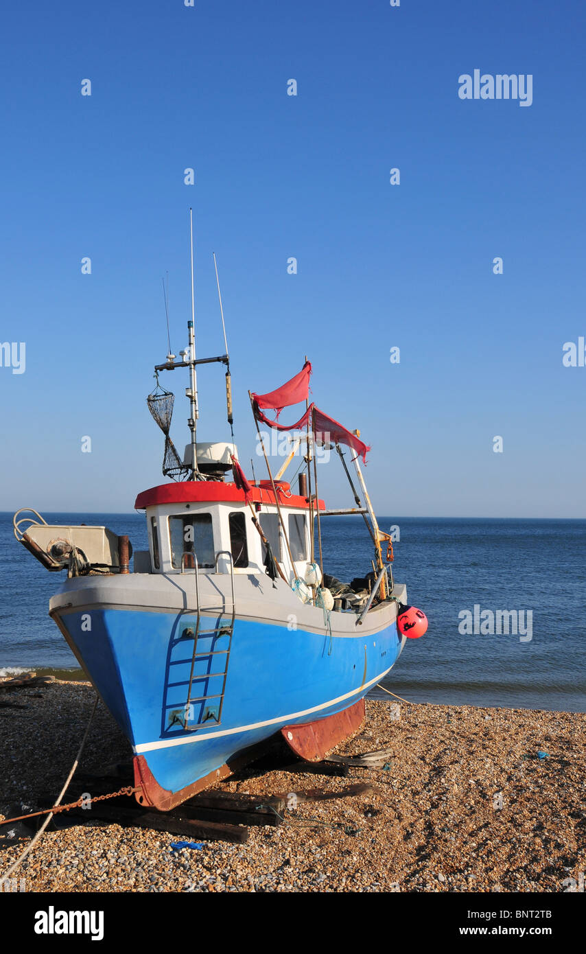 Fishing trawler pulled out of the sea and up onto the beach. Image taken at Hythe, near Folkestone in Kent, UK - Stock Image