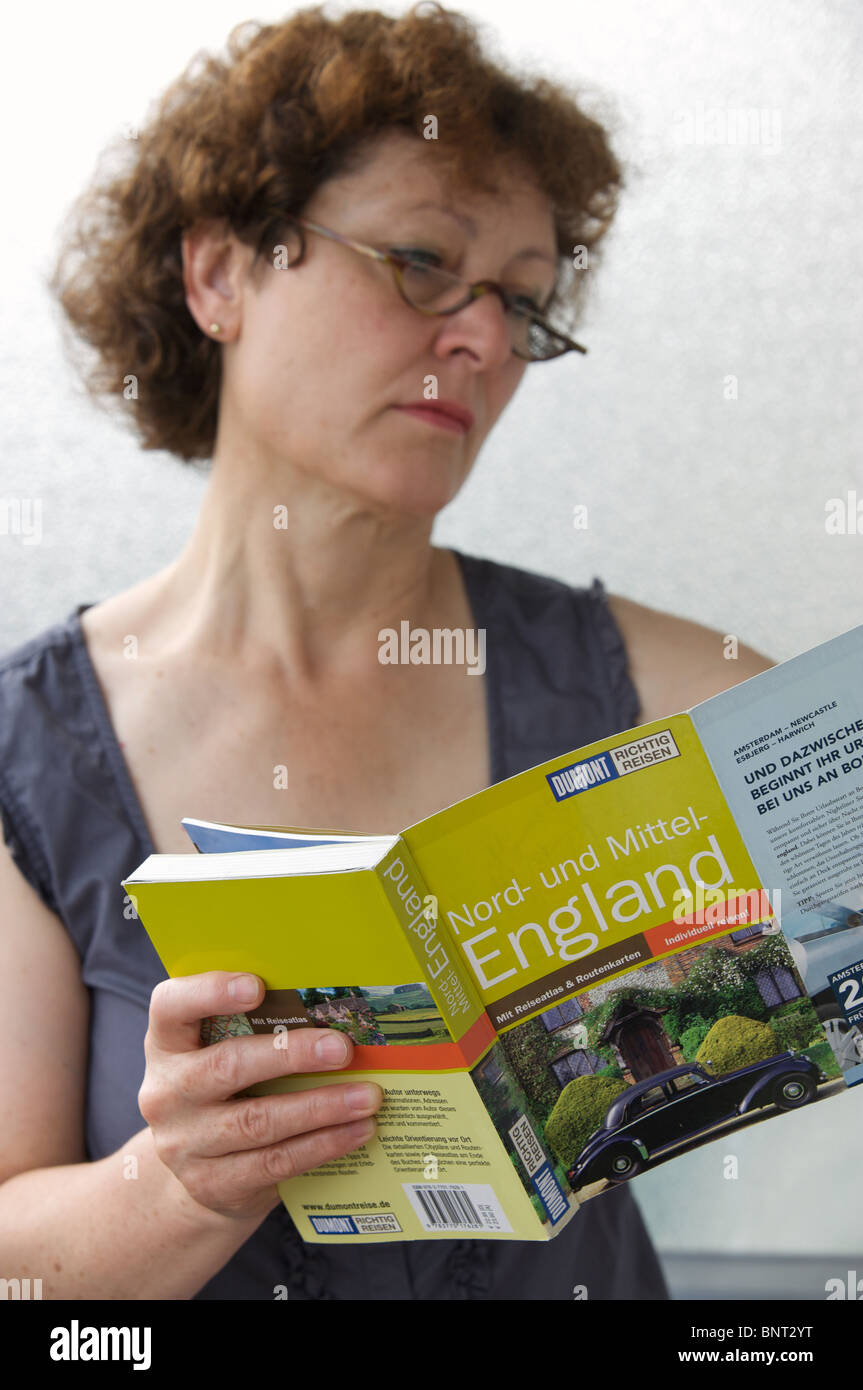German woman reading a travel guide of England - Stock Image