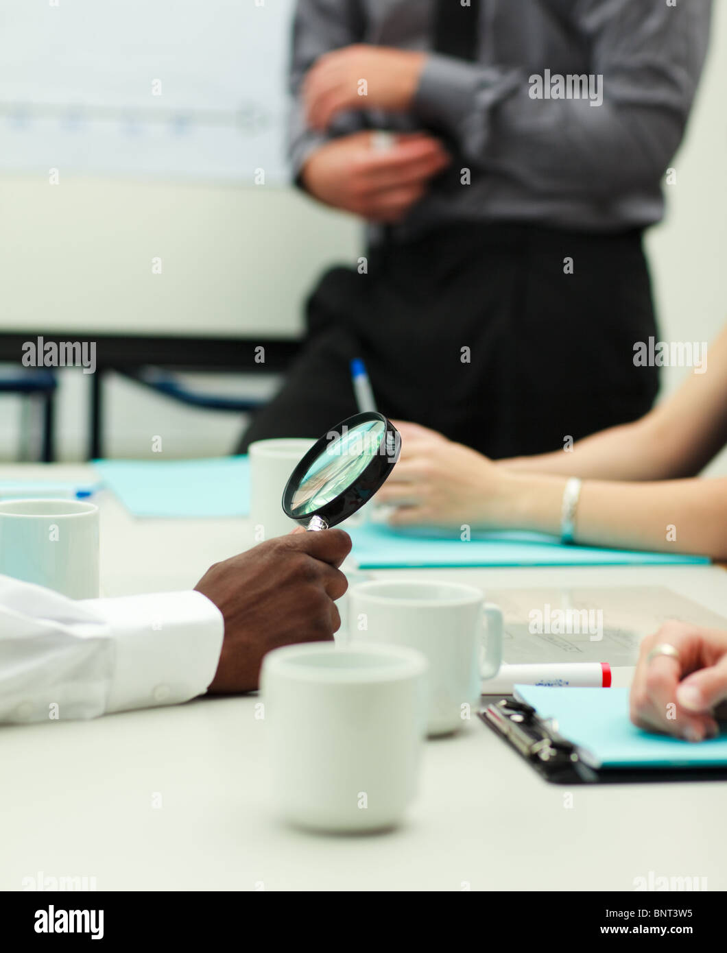 Businessman holding a magnifying glass Stock Photo