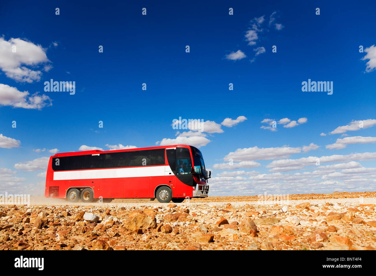 A bus drives along a dirt road in outback Queensland, near Birdsville, Queensland, AUSTRALIA. - Stock Image
