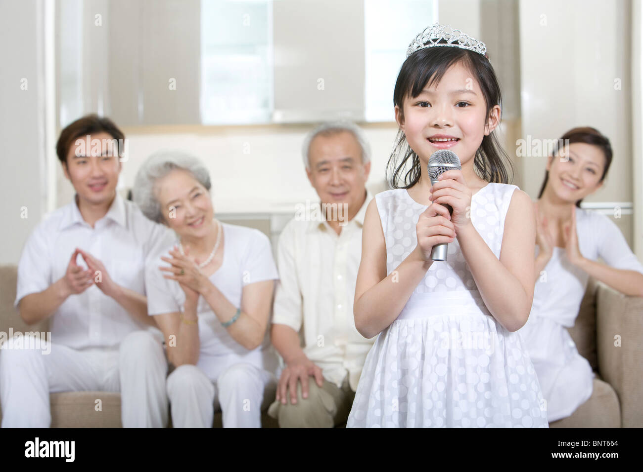 Little girl sings in front of her family - Stock Image