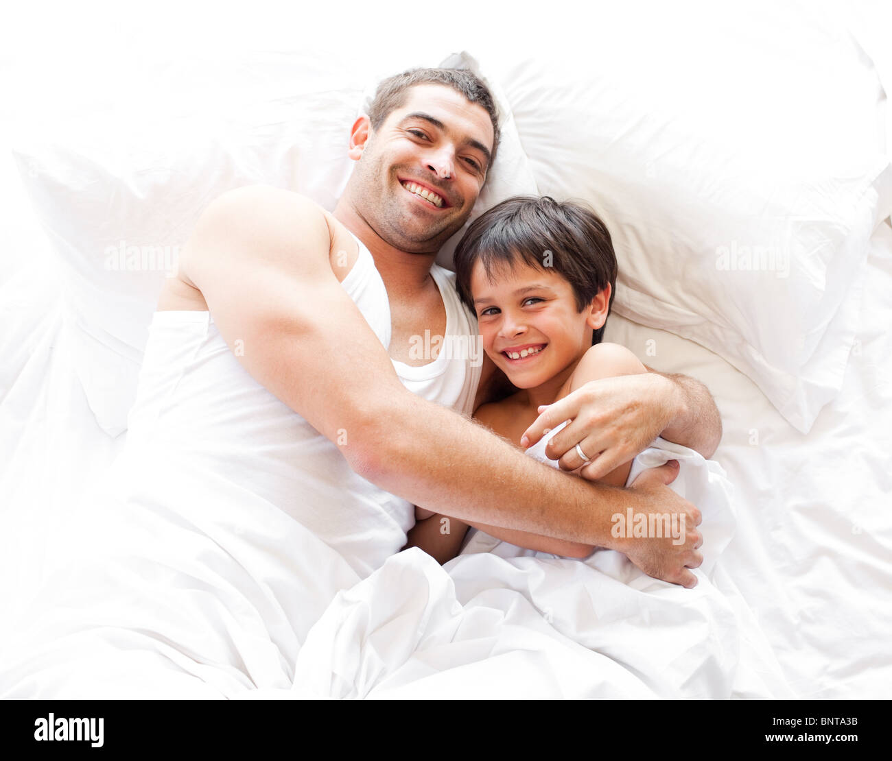 Smiling father and his son looking at the camera on the bed Stock Photo