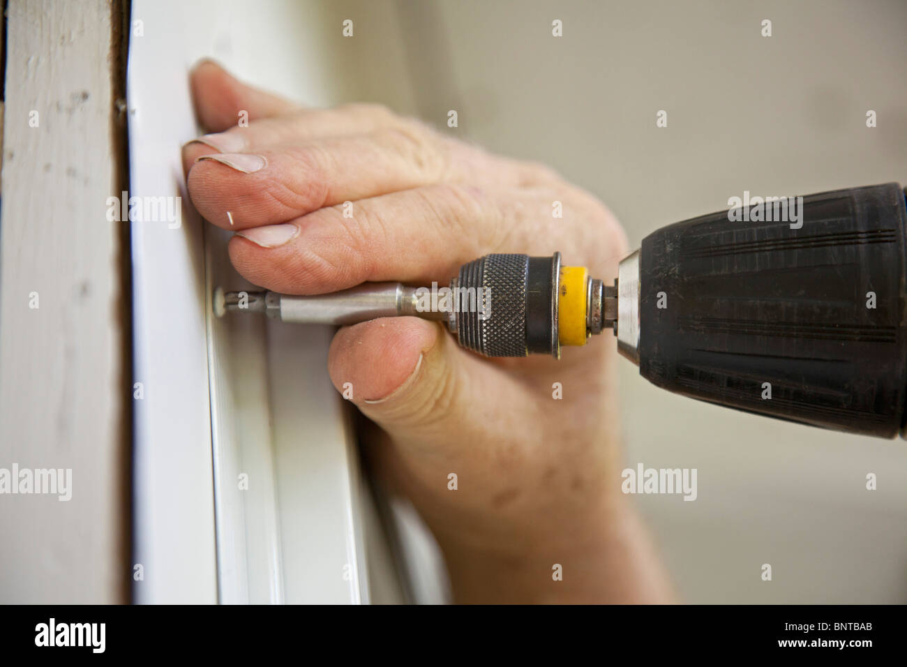 Prairieville, Michigan - A man uses a cordless drill to install a window on a rural cottage. - Stock Image