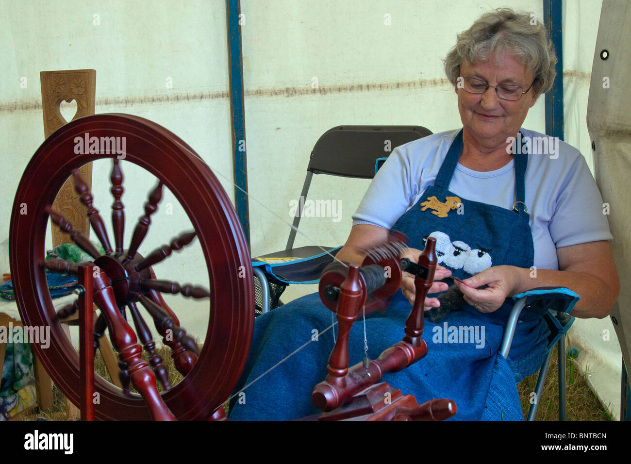 Old dear using an ancient spinning wheel, showing the art of wool spinning - Stock Image