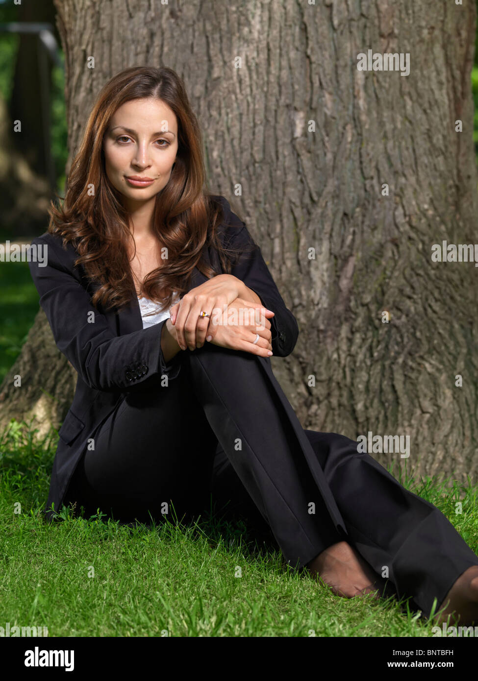 Young Attractive Businesswoman Sitting Barefoot On Green