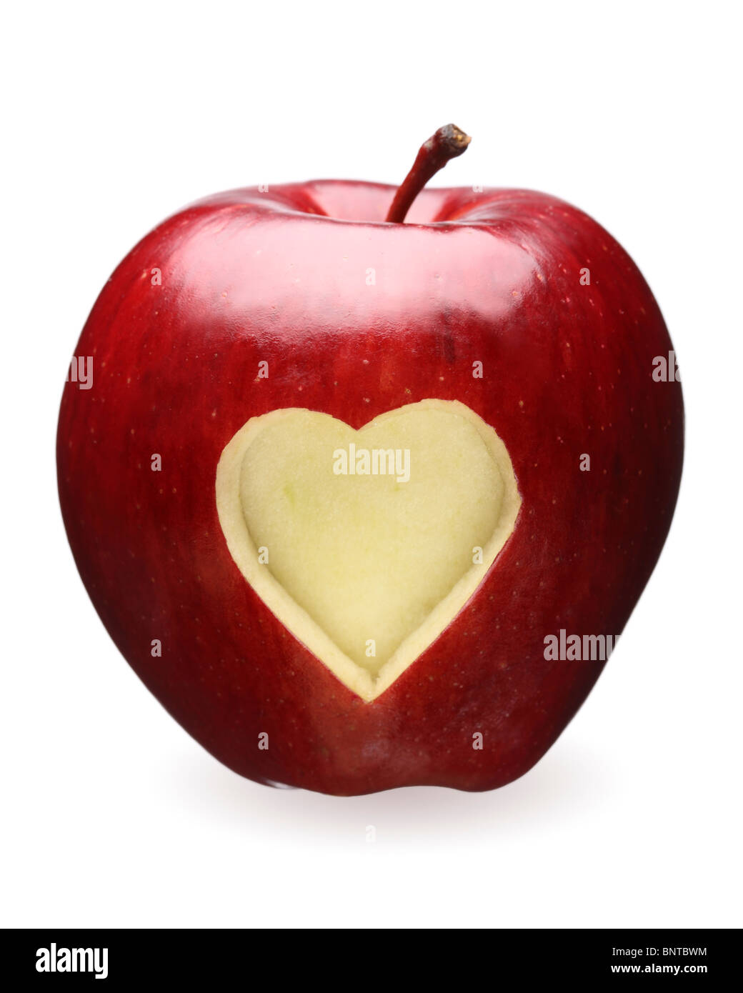 Heart shape carved out of red apple Stock Photo