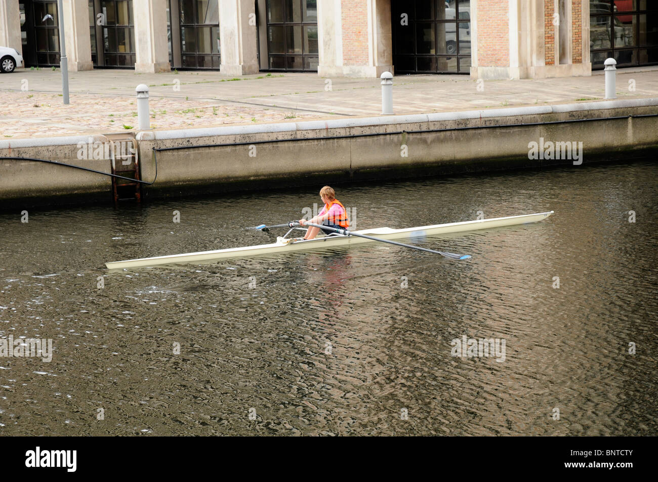 Woman rowing a single skull in Dunkirk, France - Stock Image
