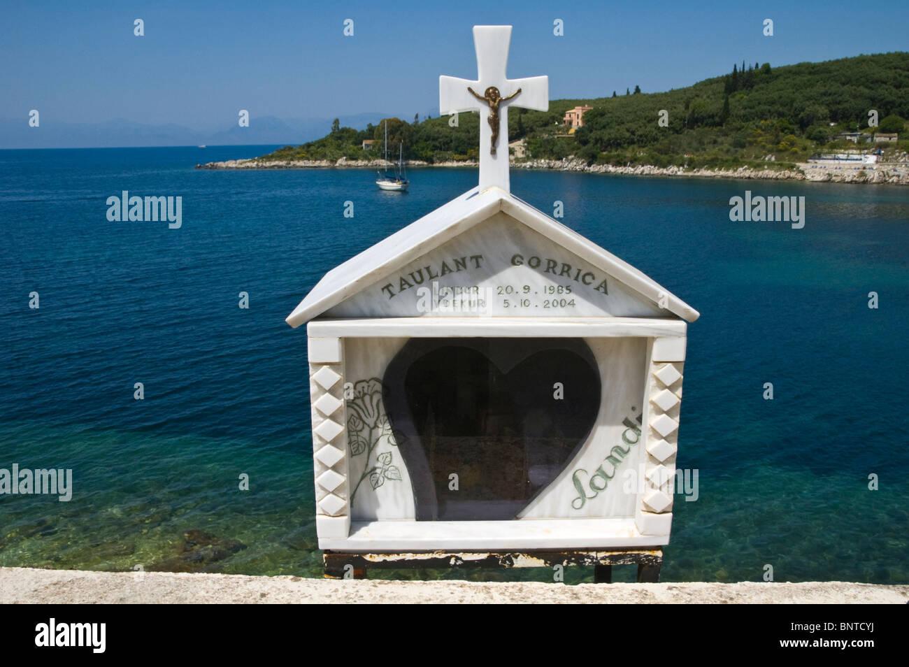 Roadside shrine overlooking bay at Kassiopi on the Greek Mediterranean island of Corfu Greece GR - Stock Image