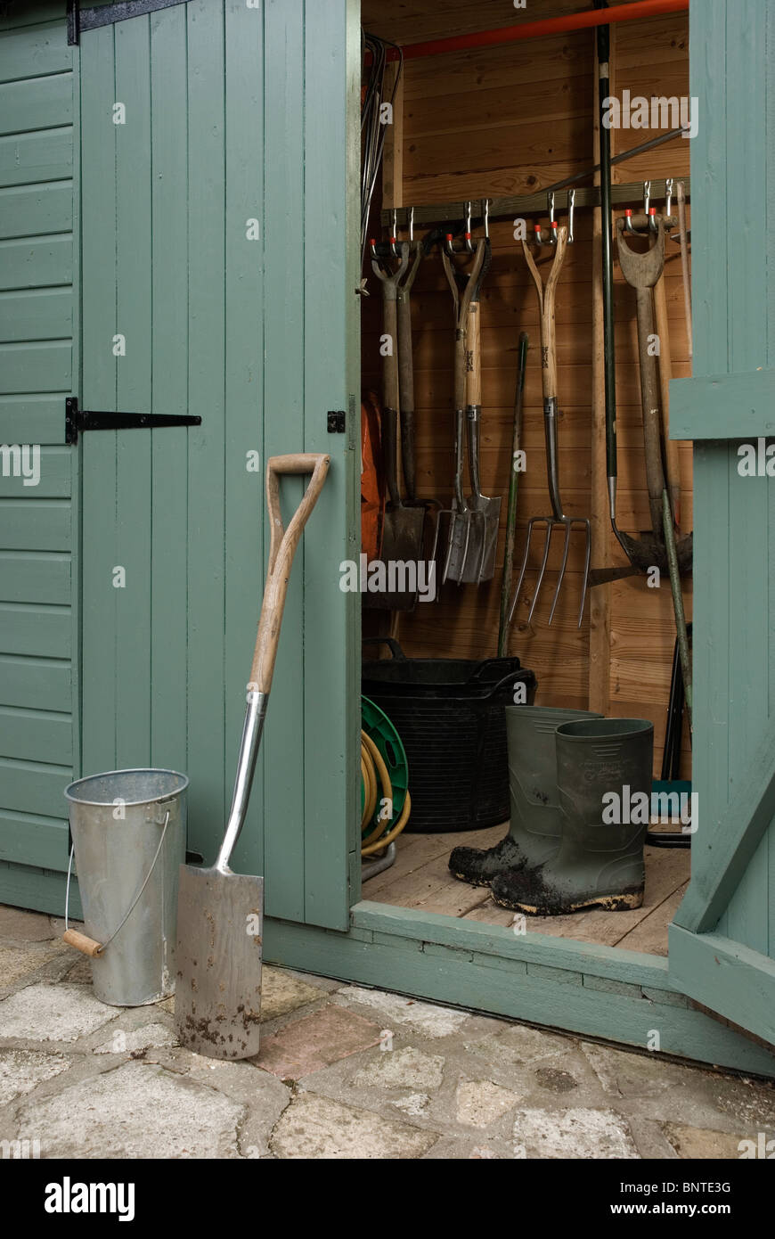 Spade and muddy boots by a garden shed. - Stock Image