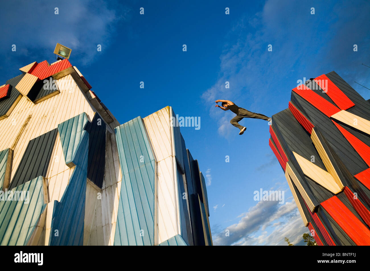 A man practices the urban sport of parkour (free running) across sculptures in Adelaide, South Australia, AUSTRALIA. - Stock Image