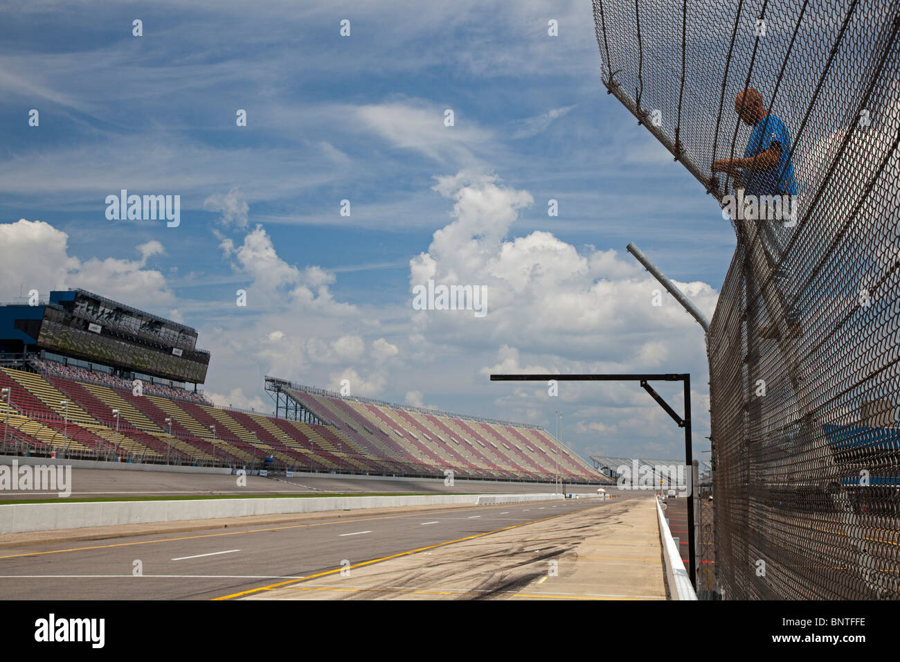Worker Repairs Fence at Michigan International Speedway - Stock Image