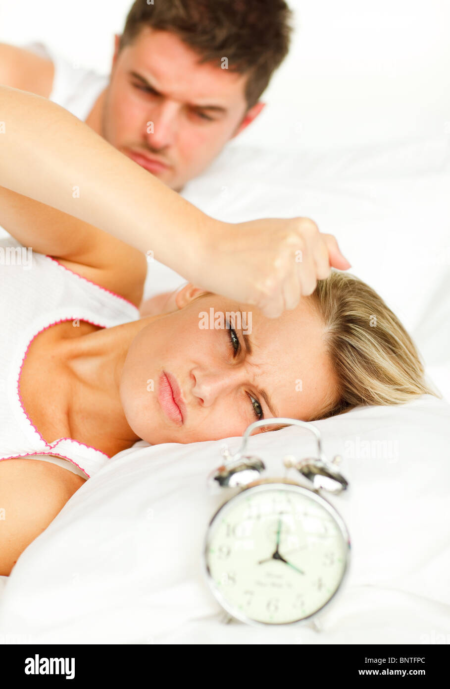 attractive man and angry woman in bed looking at the alarm clock