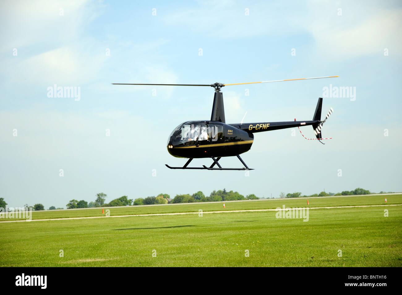 Robinson R44 helicopter just about to land at Sywell aerodrome - Stock Image
