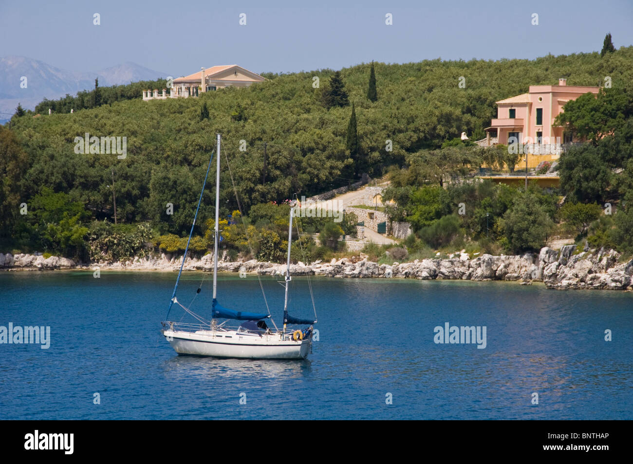 Luxury villas on wooded hillside with sailing yacht moored in bay at Kassiopi on the Greek Mediterranean island - Stock Image