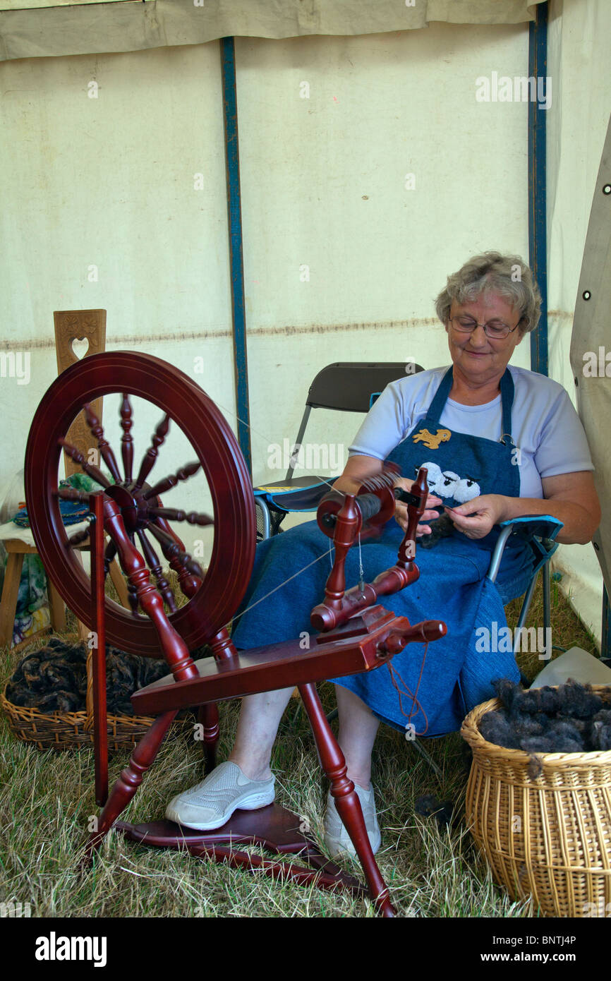 Old lady demonstrating a spinning wheel at Revesby Country Fair, Lincolnshire, England, wool spun to make balls - Stock Image