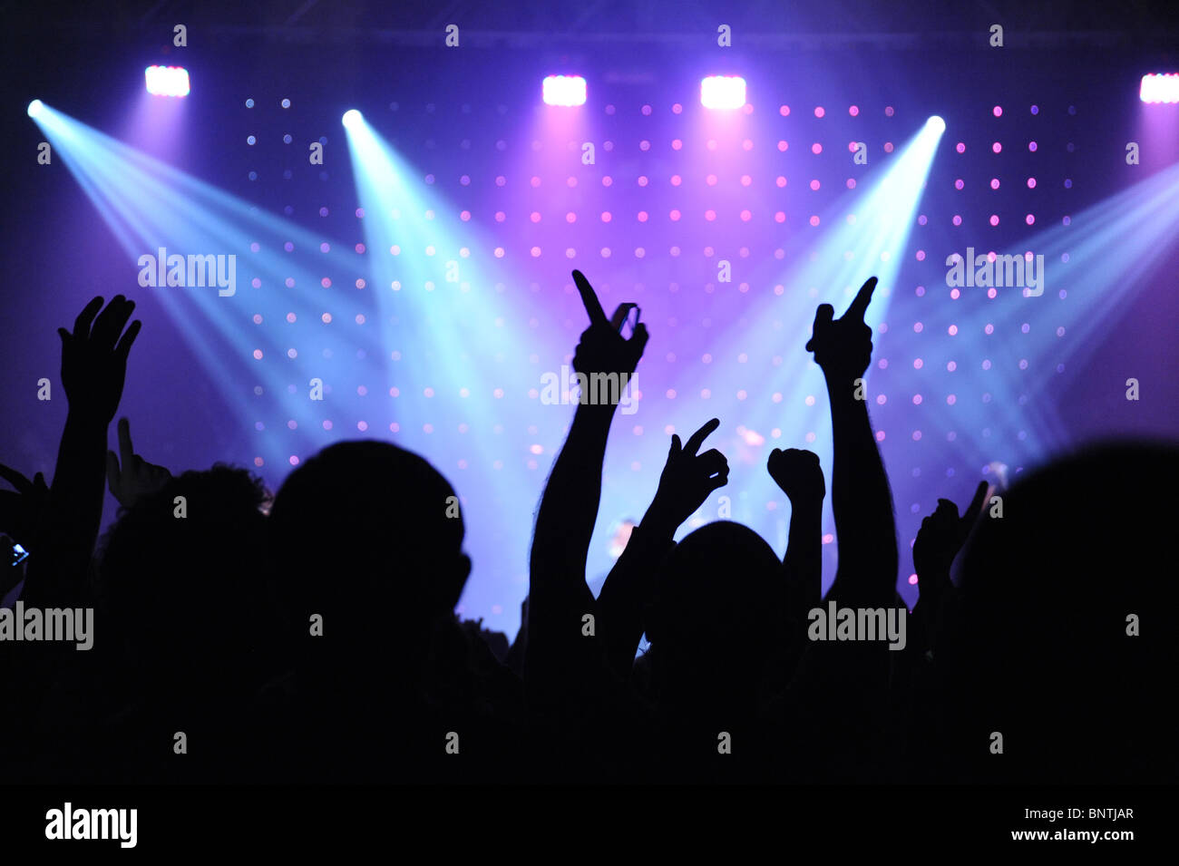 People at a concert silhouetted by the lights - Stock Image