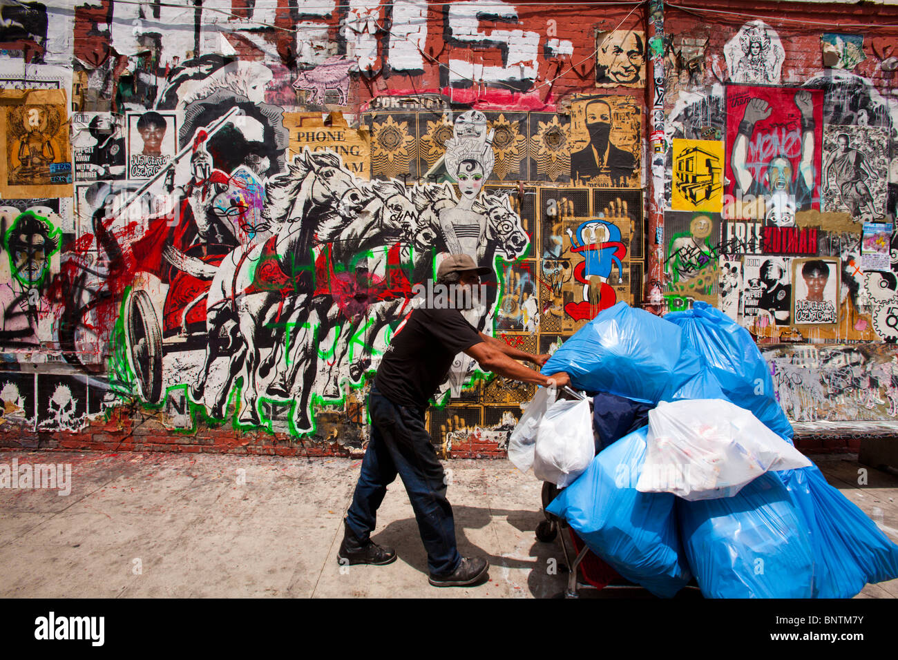 homeless (probably) man with shopping cart walks by a street art mural, Los Angeles, California, United States of - Stock Image