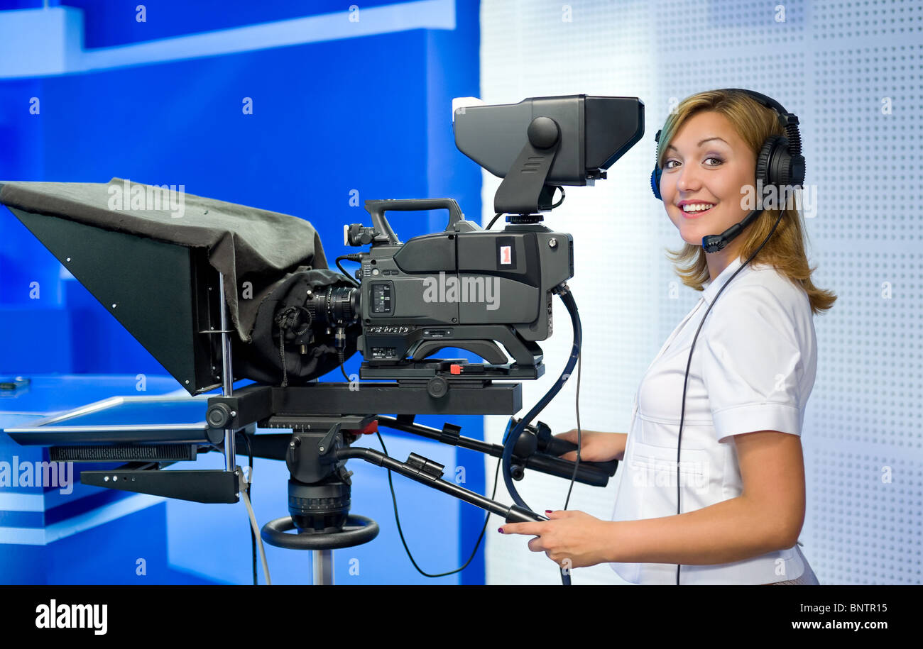 a female cameraman at a studio smiles into camera - Stock Image