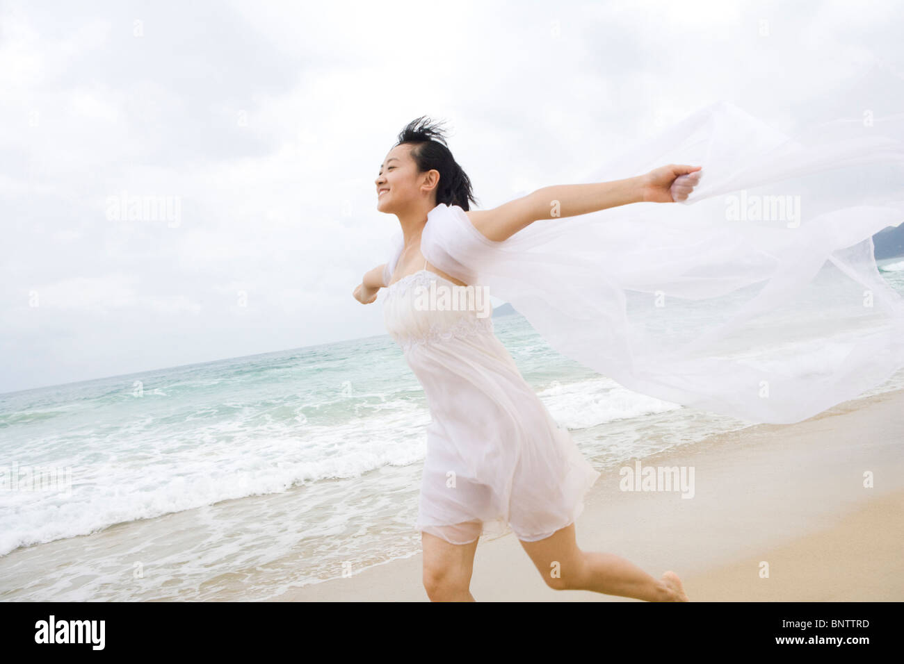 Portrait of a young woman running along the beach Stock Photo