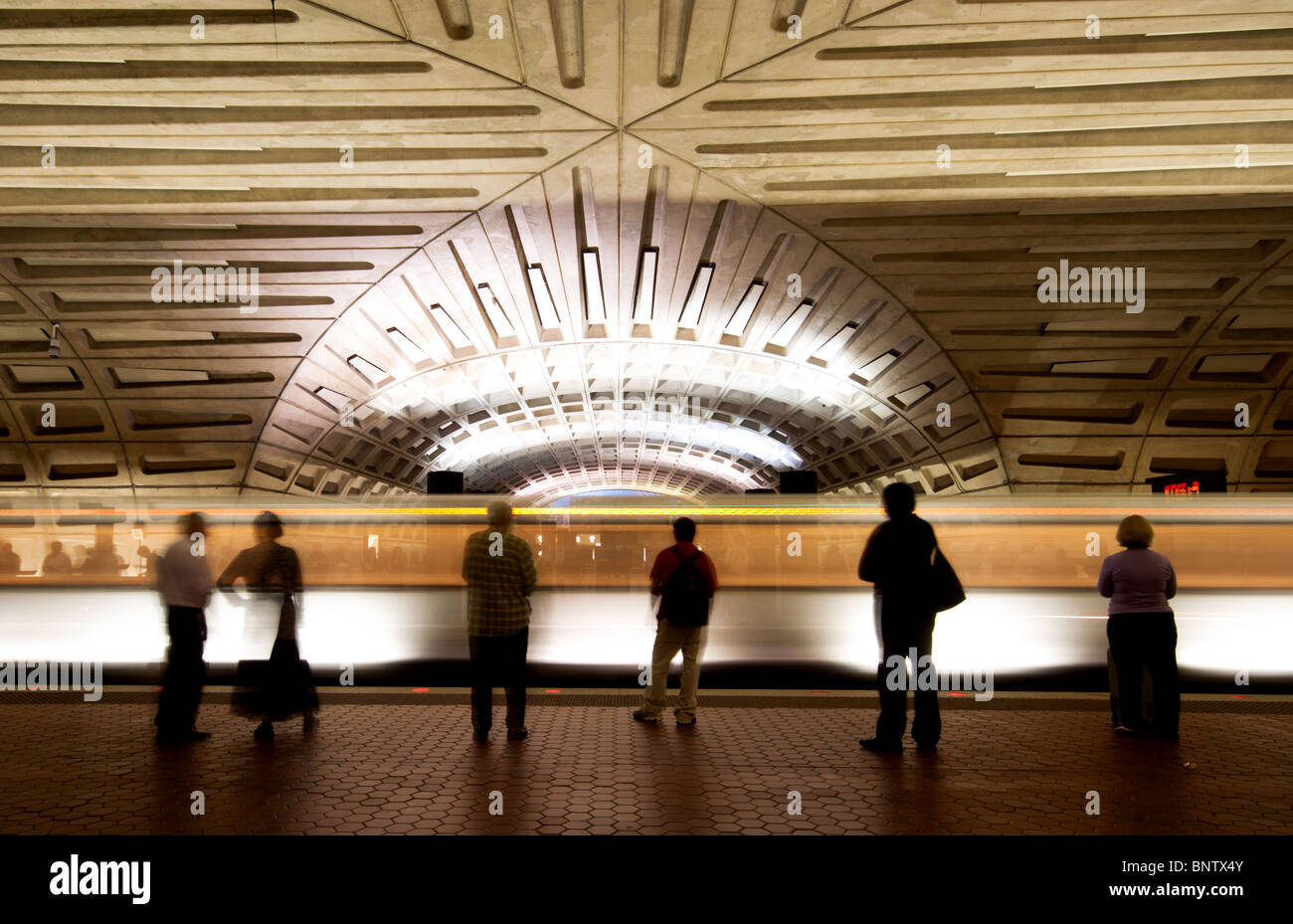 Commuters/passengers waiting for a train on a metro station platform as a train leaves the station in Washington - Stock Image