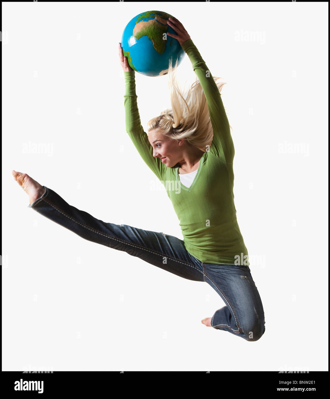 Woman jumping in air while holding globe Stock Photo
