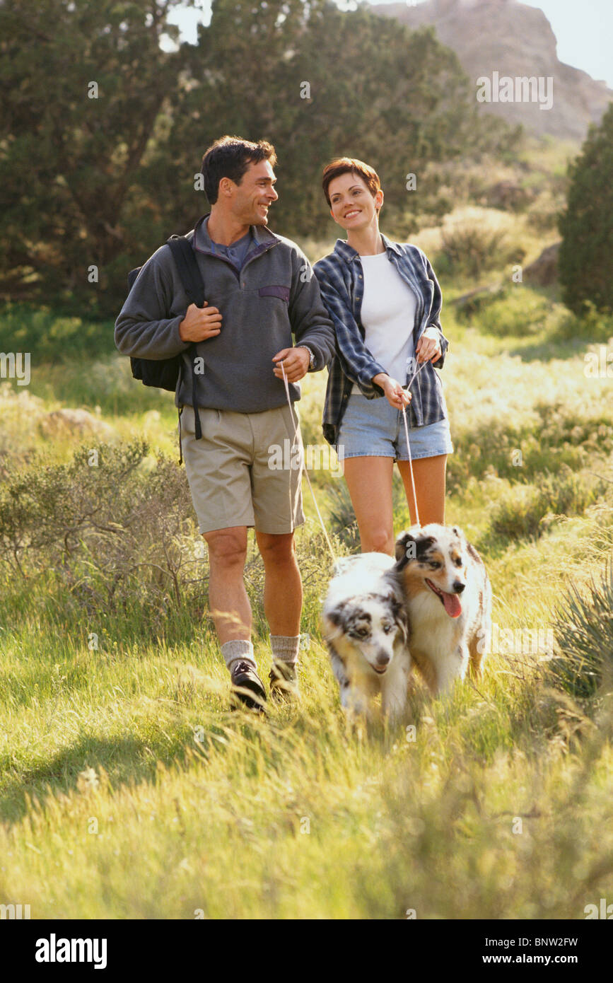 Couple walking their dogs in the countryside Stock Photo