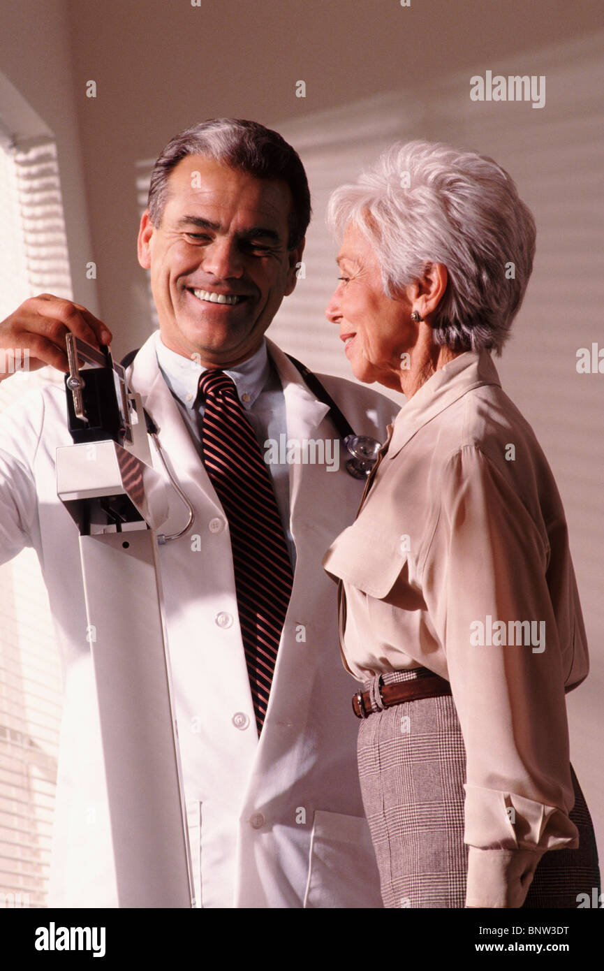 Doctor weighing senior patient - Stock Image