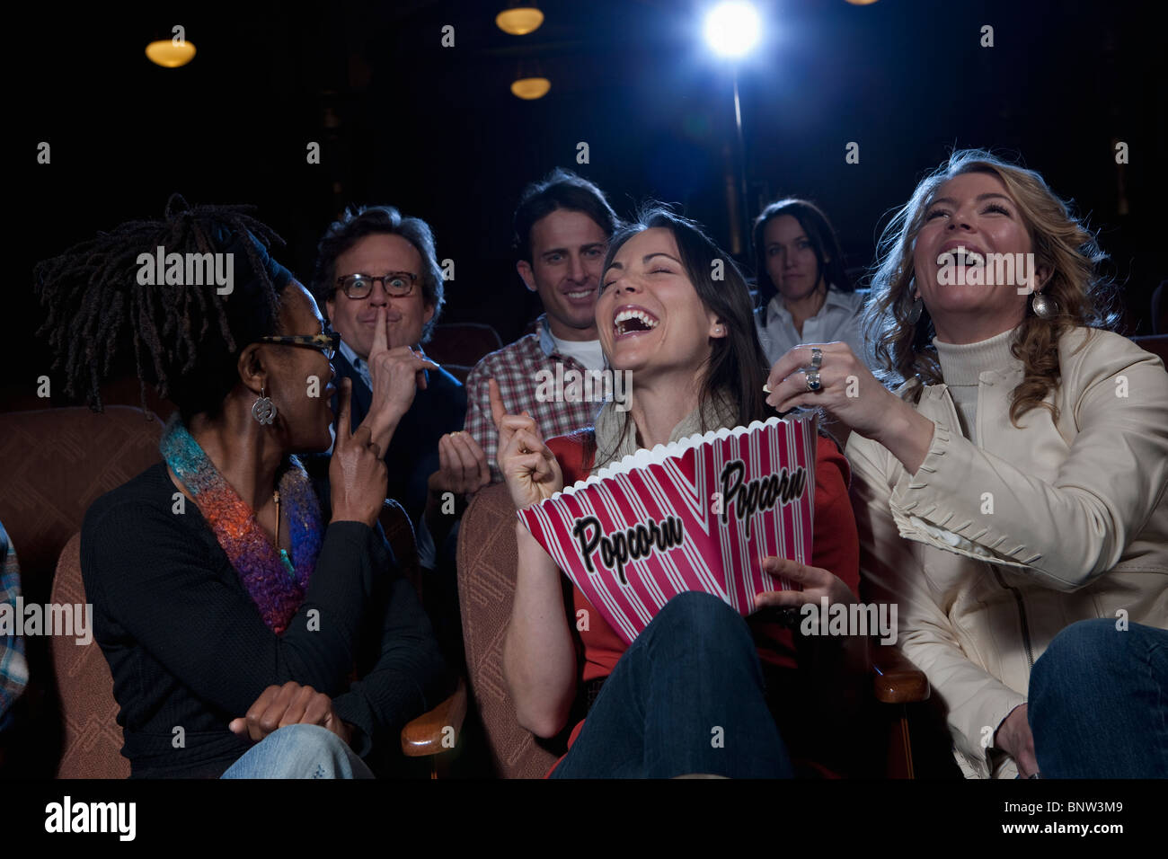 Women laughing loudly in movie theatre - Stock Image