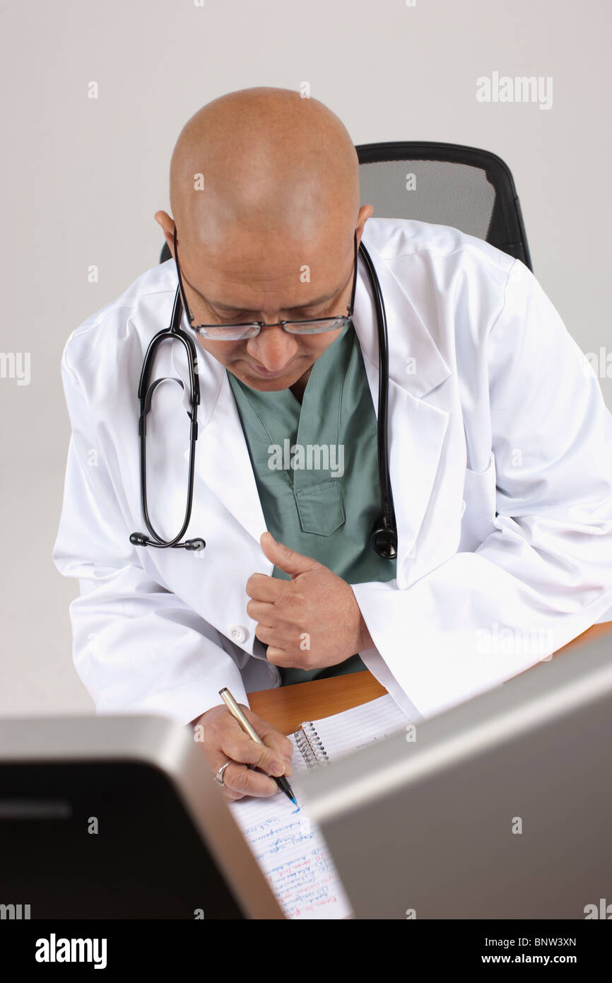 Doctor working at his desk Stock Photo